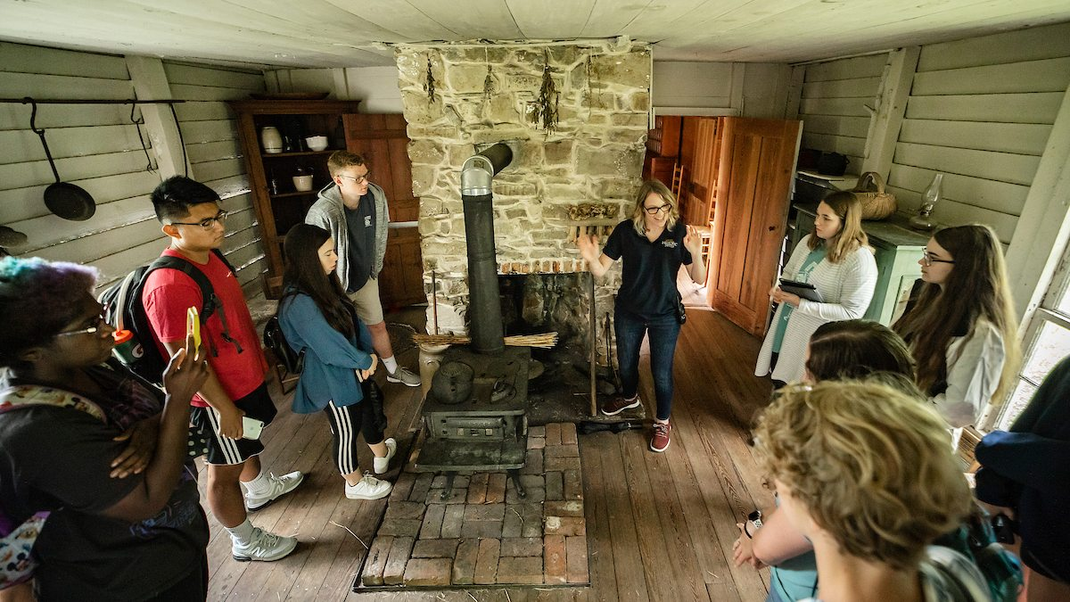 Students stand in the Duke Homestead State Historic Site listening to a speaker.