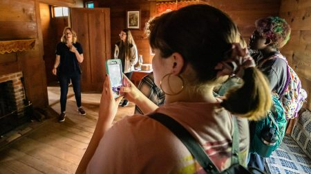 A student takes a photo at the Duke Homestead State Historic Site.