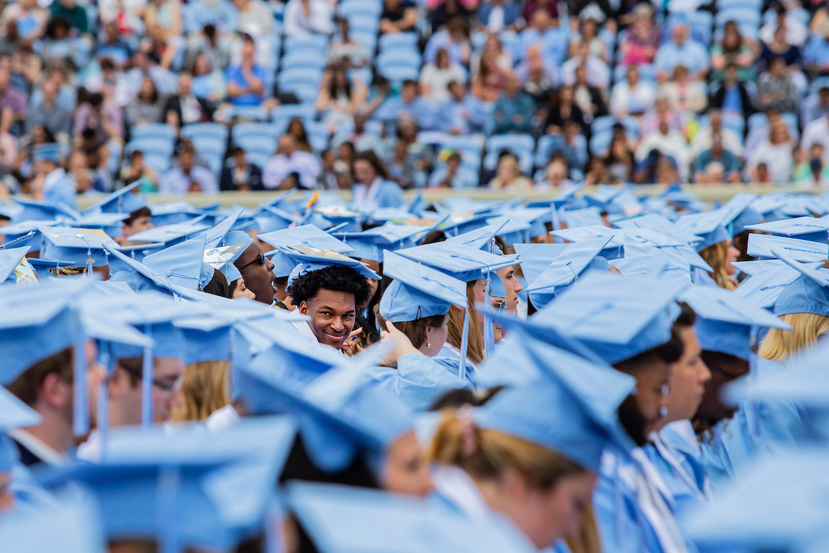 Students sit in their caps and gowns during commencement.