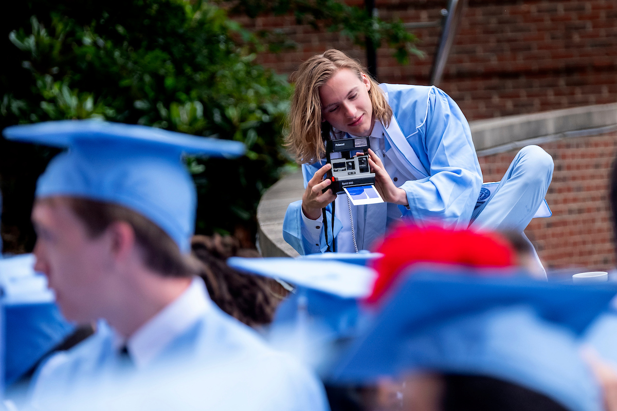 A student takes a polariod picture.