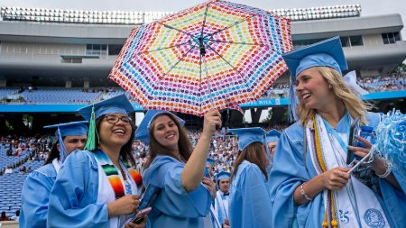 A student, holding an umbrella, poses for a photo as they walk into Commencement.