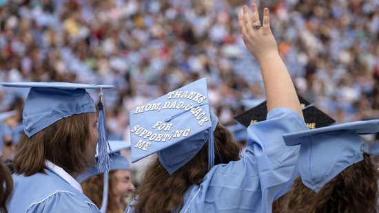 A student waves during Commencement.