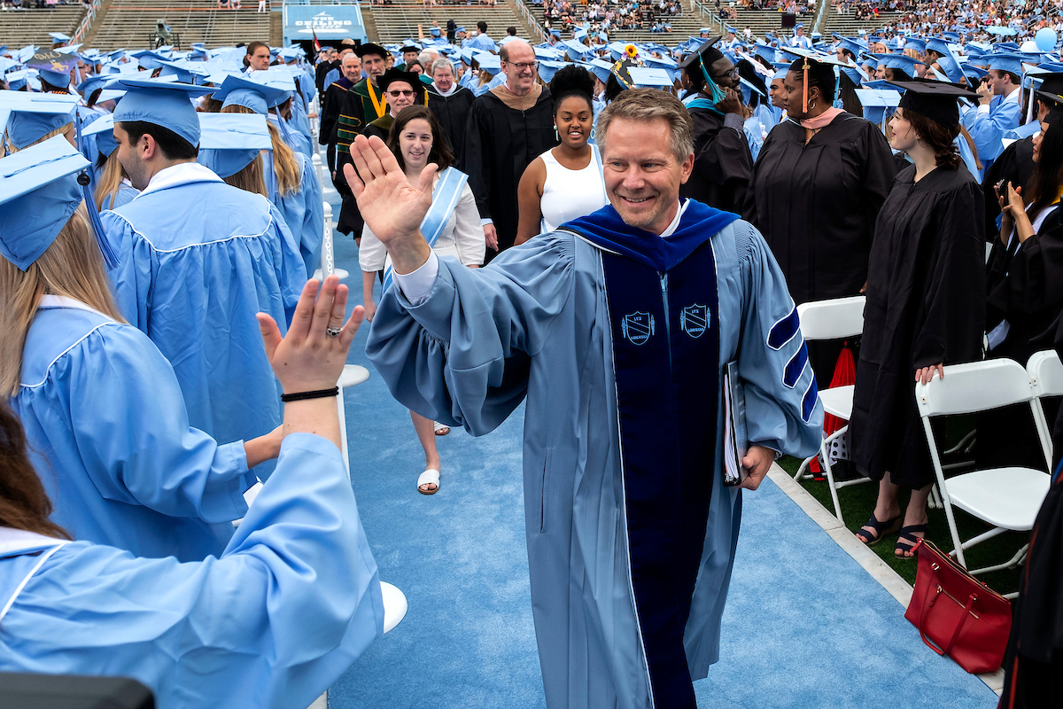 Interim Chancellor Kevin M. Guskiewicz high-fives students while walking into commencement.