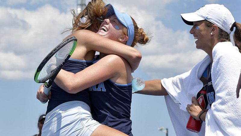 The women's tennis team celebrates.