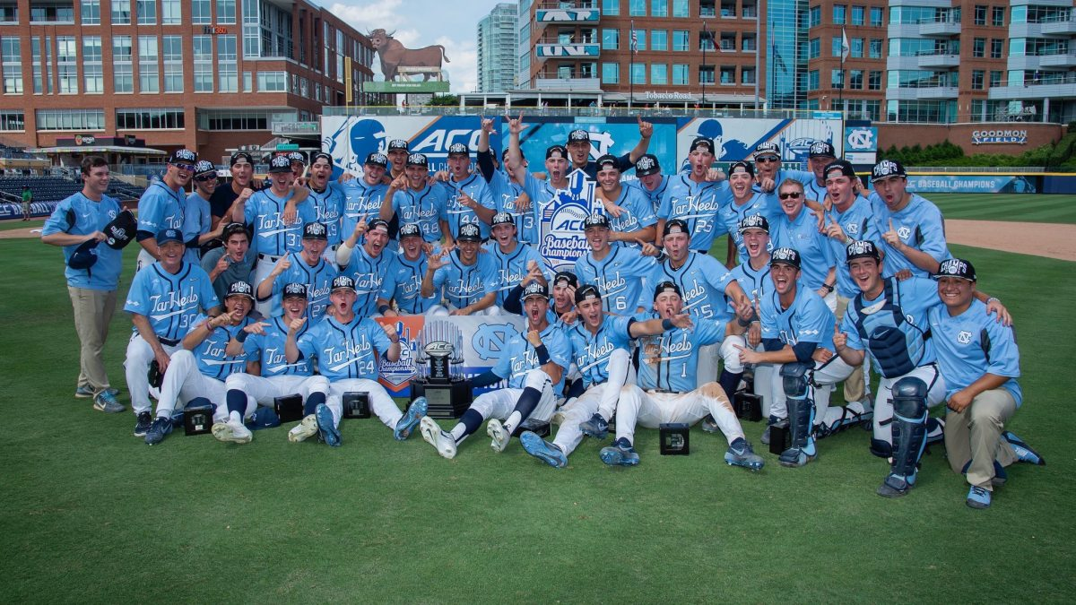 The Carolina men's basketball team poses for a photo with their ACC Championship trophy.