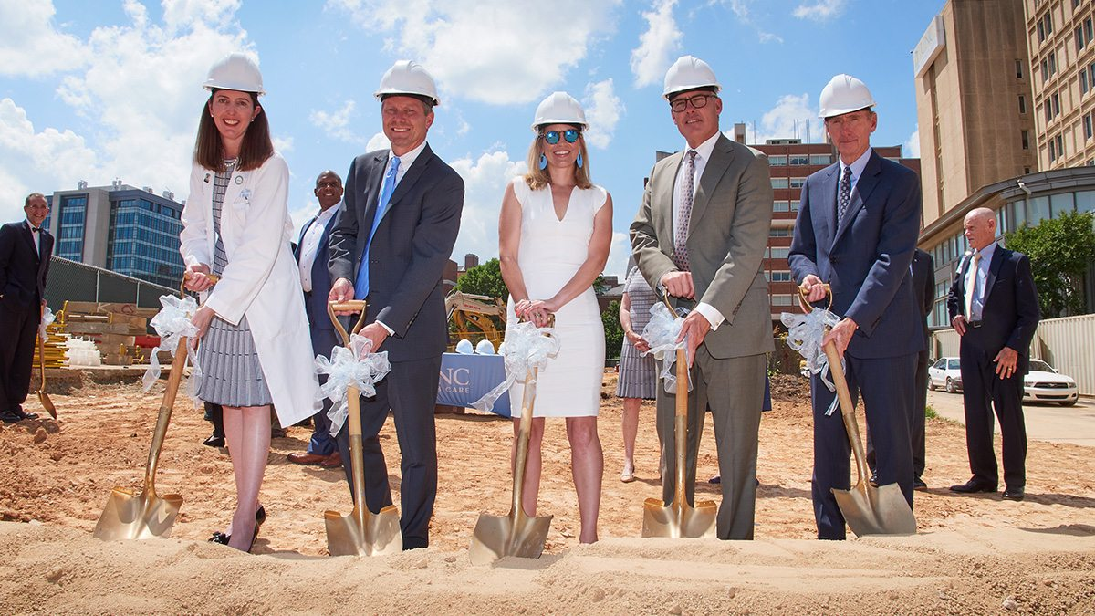 Four people with shovels break ground for the surgical center.