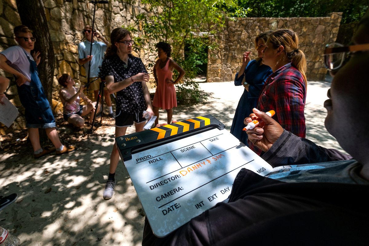A student writes on a director's clapperboard.