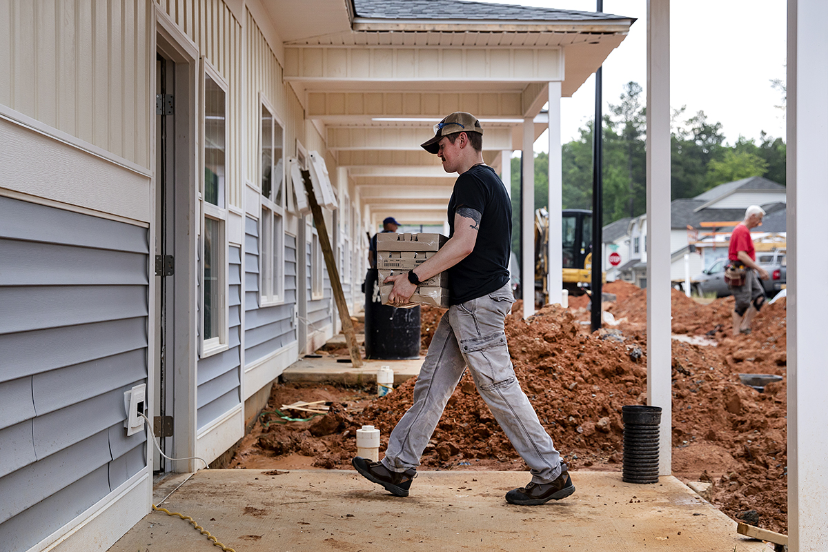 A man carries boxes through a construction site.