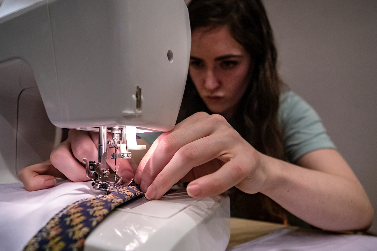 A person uses a sewing machine.