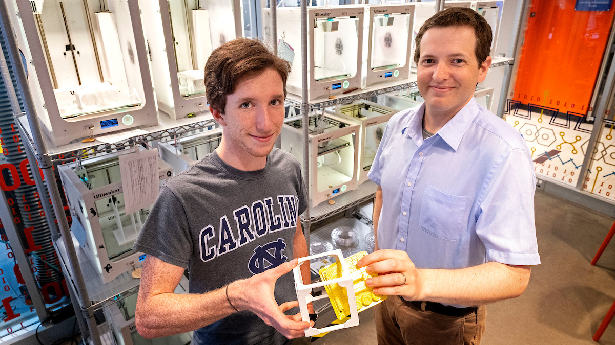 Professor and student hold up their 3D printed cube