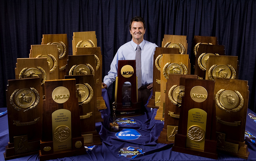 Anson Dorrance surrounded by national championship trophies.