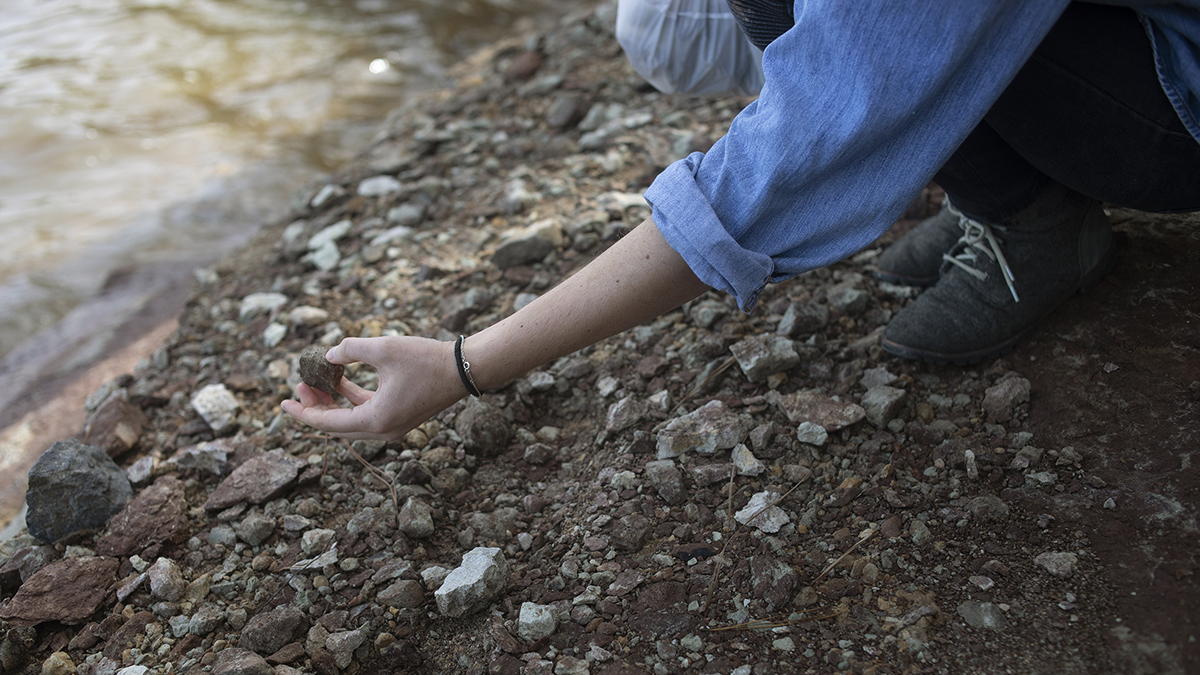 Close-up of Ayla's hand reaching for rocks on the bank of Jordan Lake