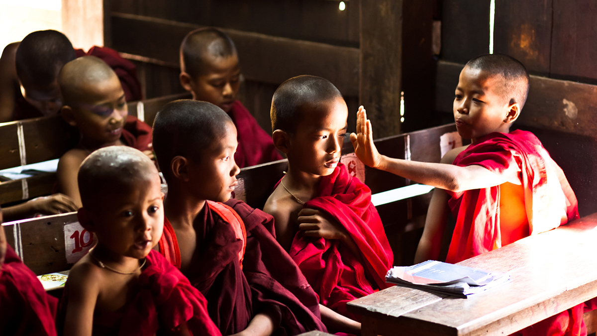 Mischievous young buddhist monks amuse themselves from the boredom of afternoon lessons while attending class