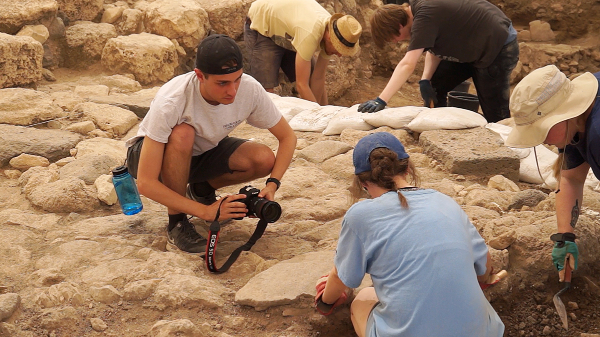 A male student takes a photo at the Huqoq dig site.
