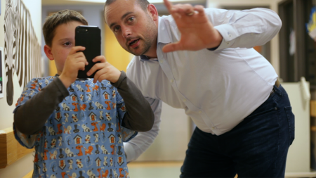A child holds a cell phone while a man points.