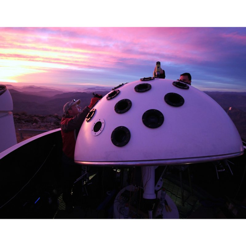 Two researchers install telescope on a rooftop at sunset