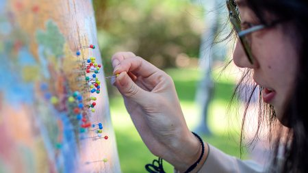 A student adds a yellow pin to the world map