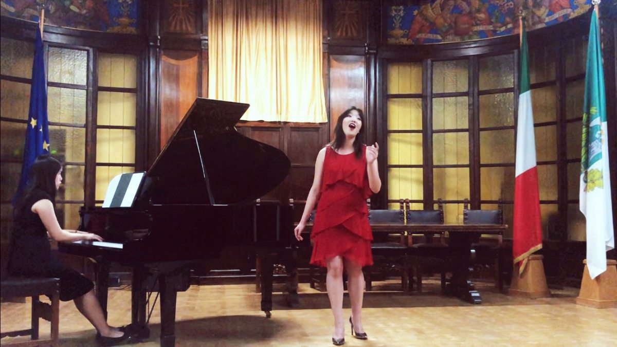 Melody stands beside a grand piano and sings