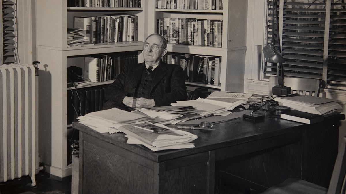 Howard Odum sits at a desk.