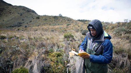 student takes notes in a field doing research.