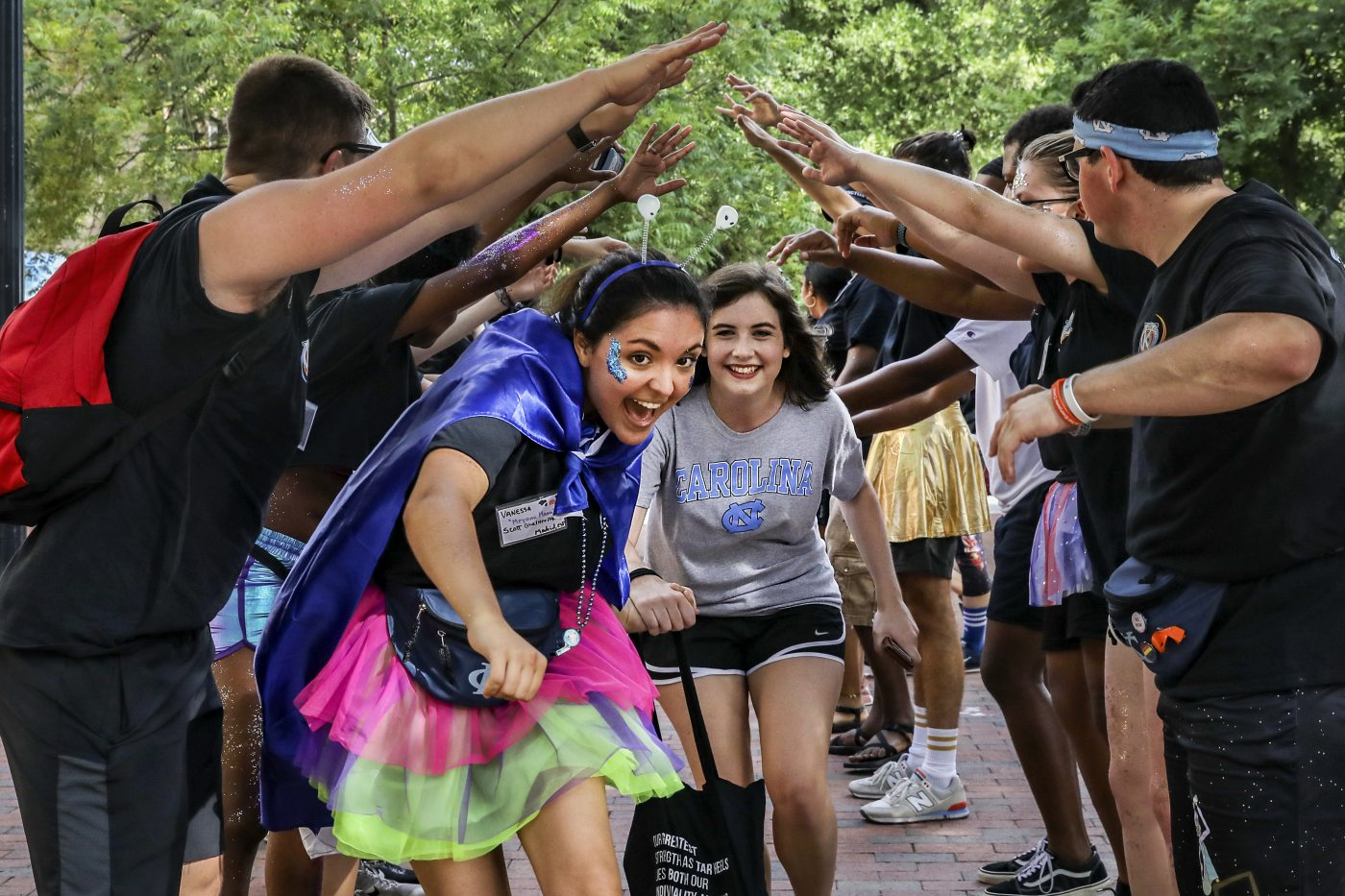 Students run through a tunnel of people.