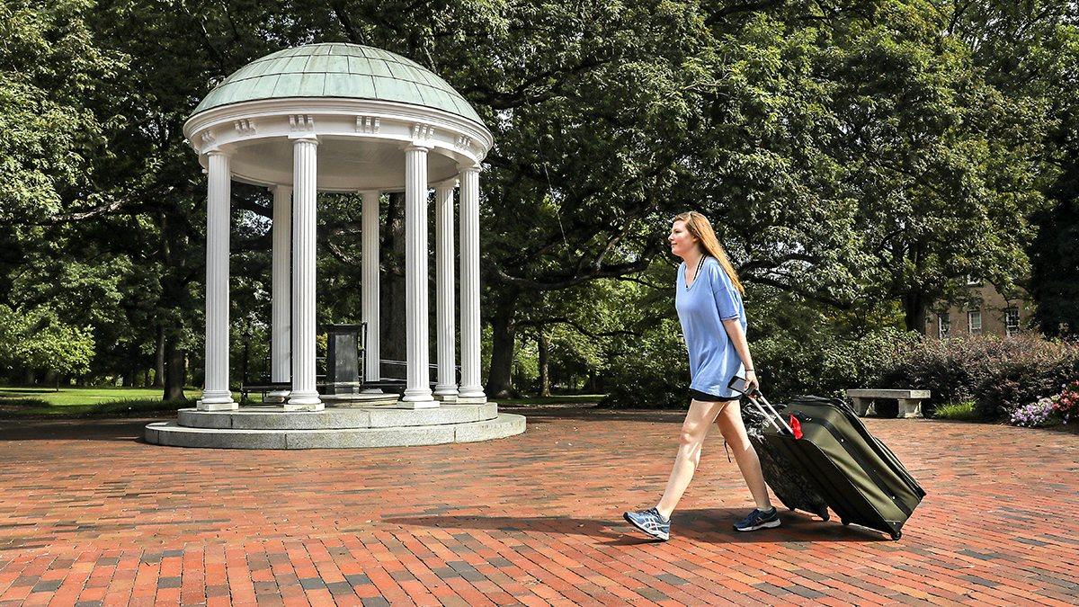 A student rolls their suitcase past the Old Well during move-in