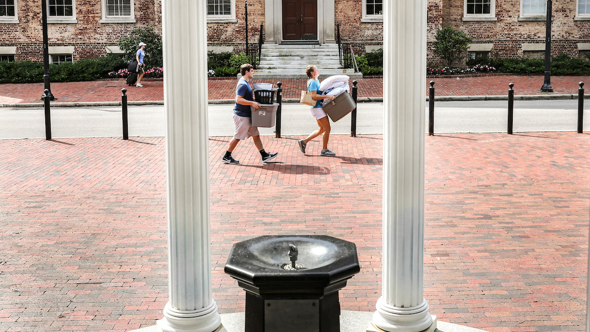 Students carry boxes near the Old Well during move in.