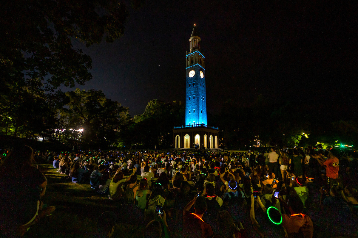 Student sit around the bell tower as it is lit in blue lights.