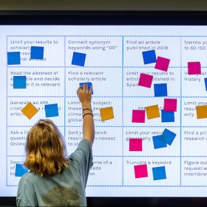 A student puts post-it notes on a board.