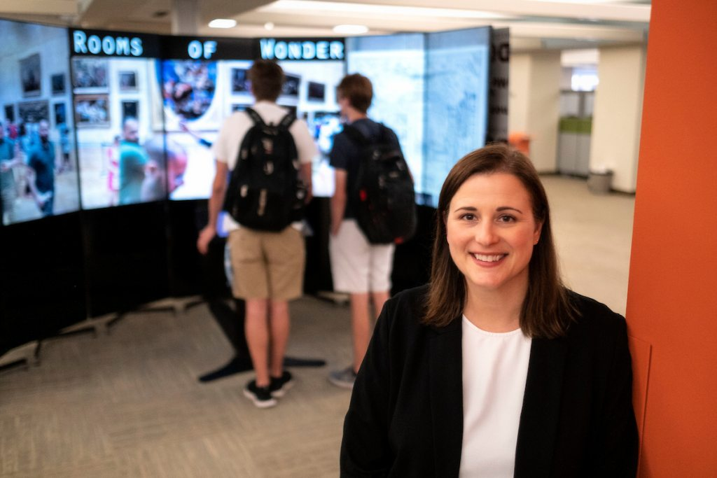 Henley stands in front of a multimedia screen with students in background