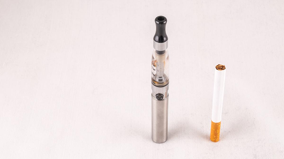 A tobacco cigarette next to an e-cigarette.