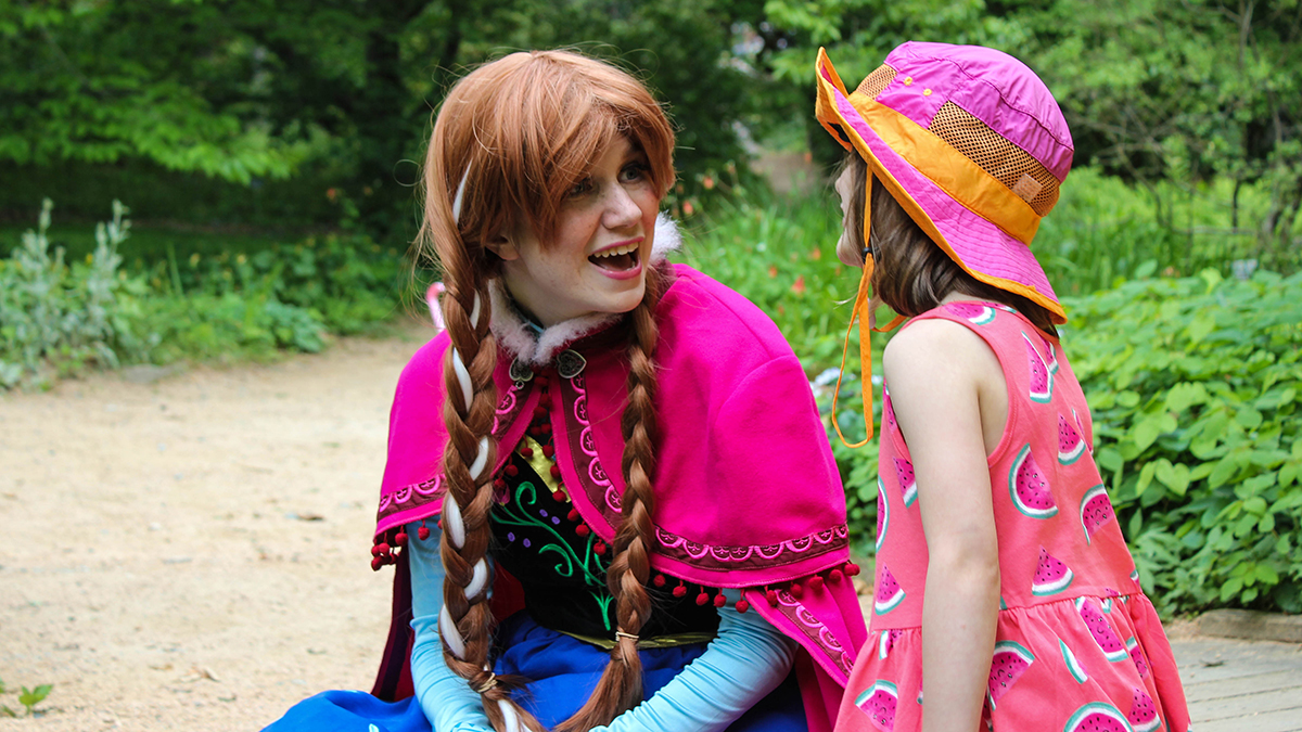 Student dressed as Disney's Elsa talks with a little girl