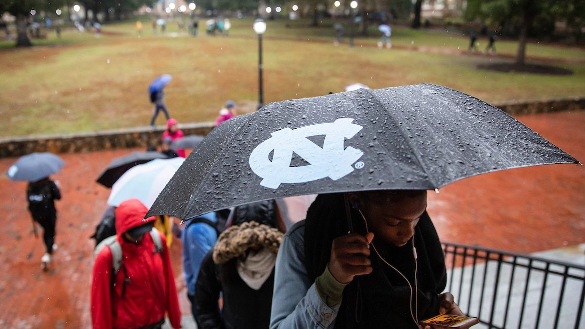 A student holds an umbrella on campus.
