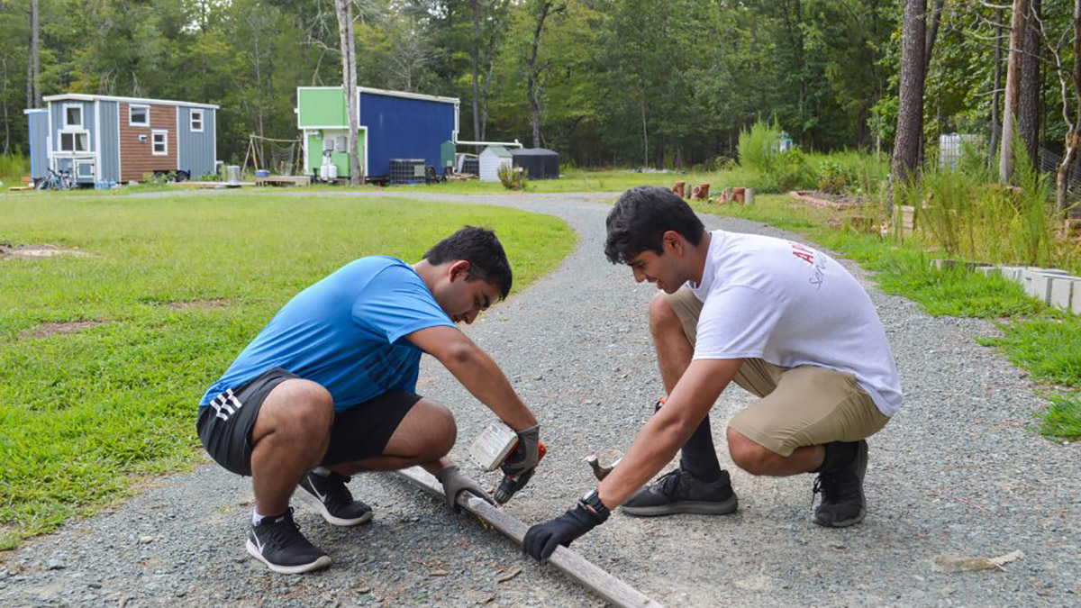 Two students kneel over wooden board in front of tiny homes