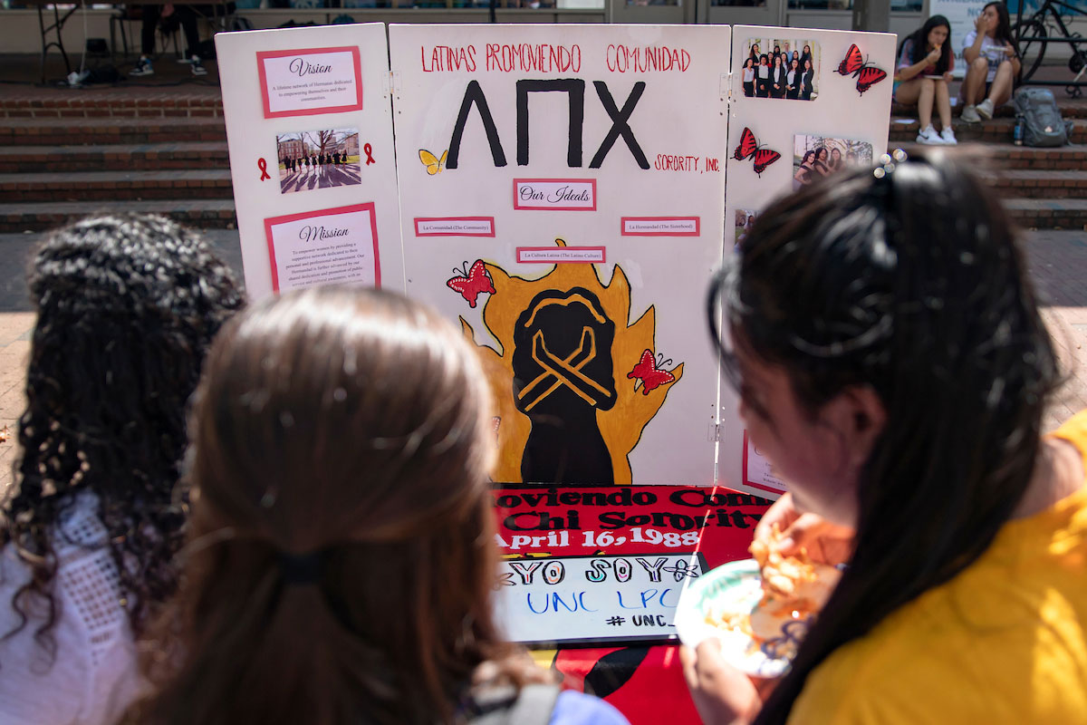 Three students look at a poster for a sorority.
