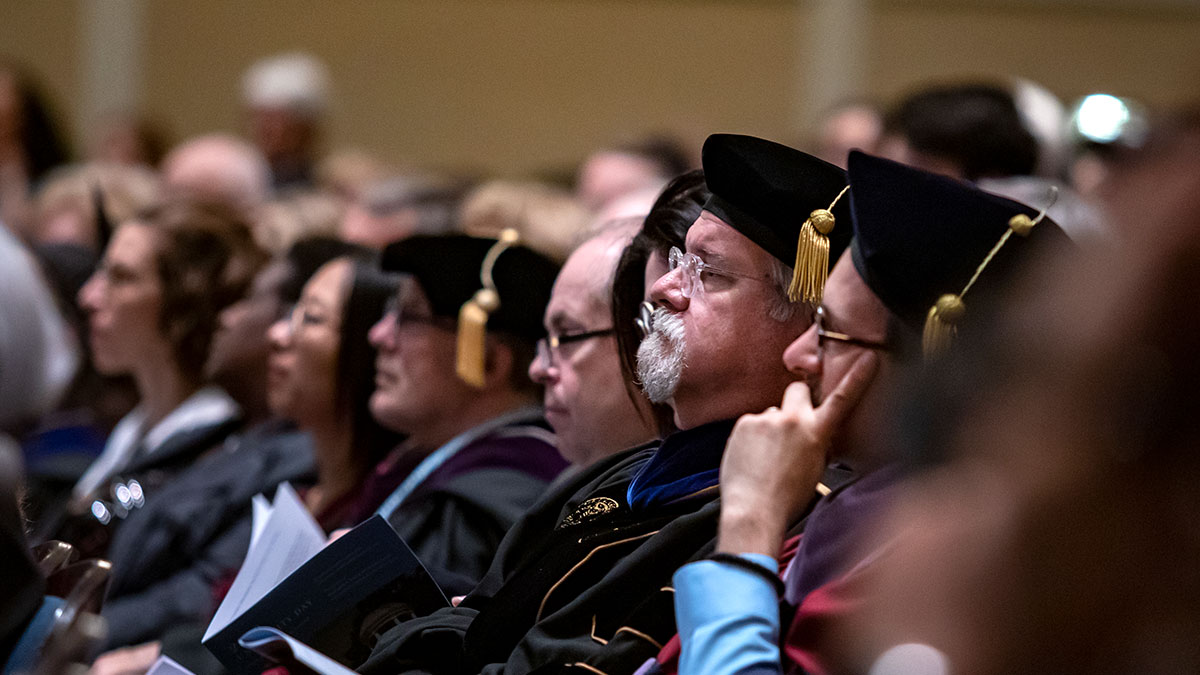 Faculty members listen during University Day.