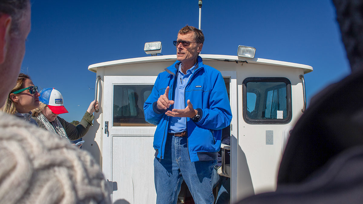 A man stands on a boat while giving a tour.
