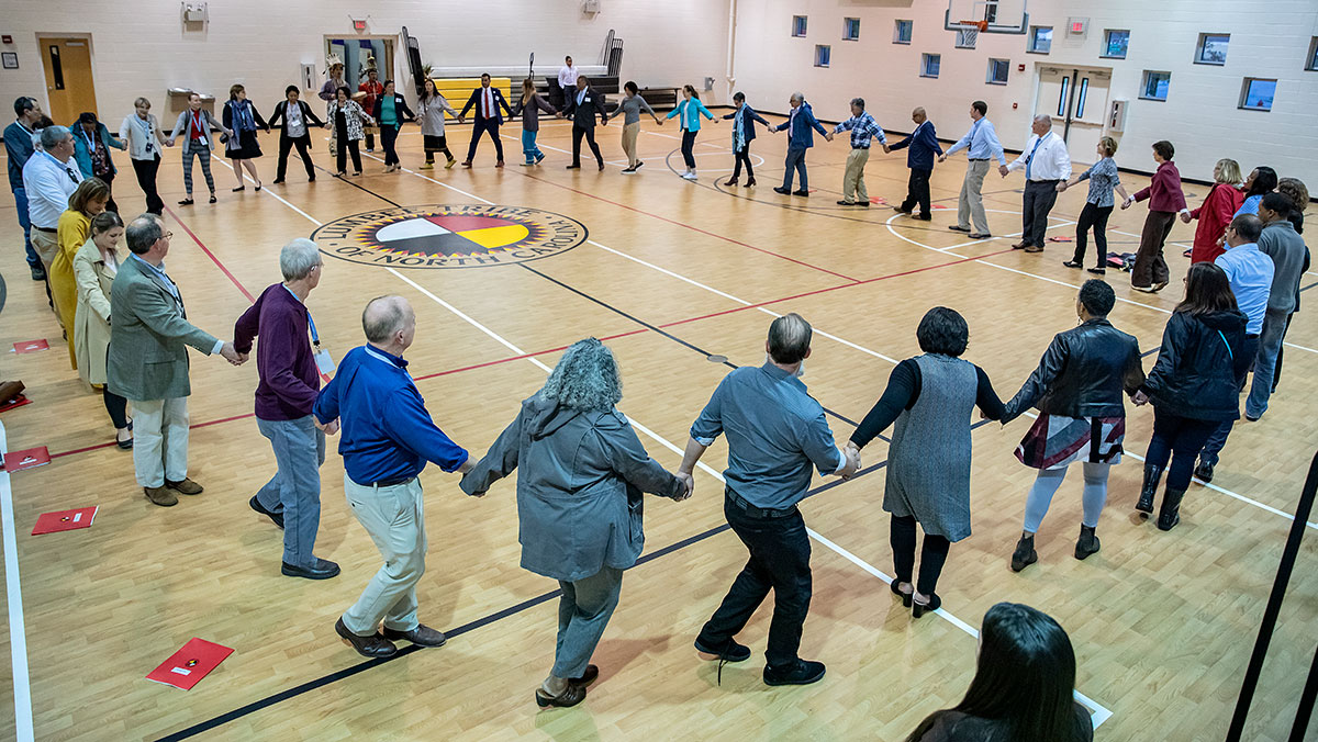 A group of faculty members hold hands in a circle during a powwow dance.