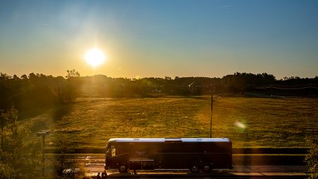 A bus parked in a parking lot at sunrise.