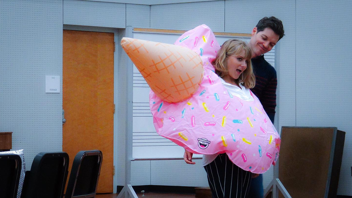 A woman wears an inflatable ice cream cone during a rehersal.