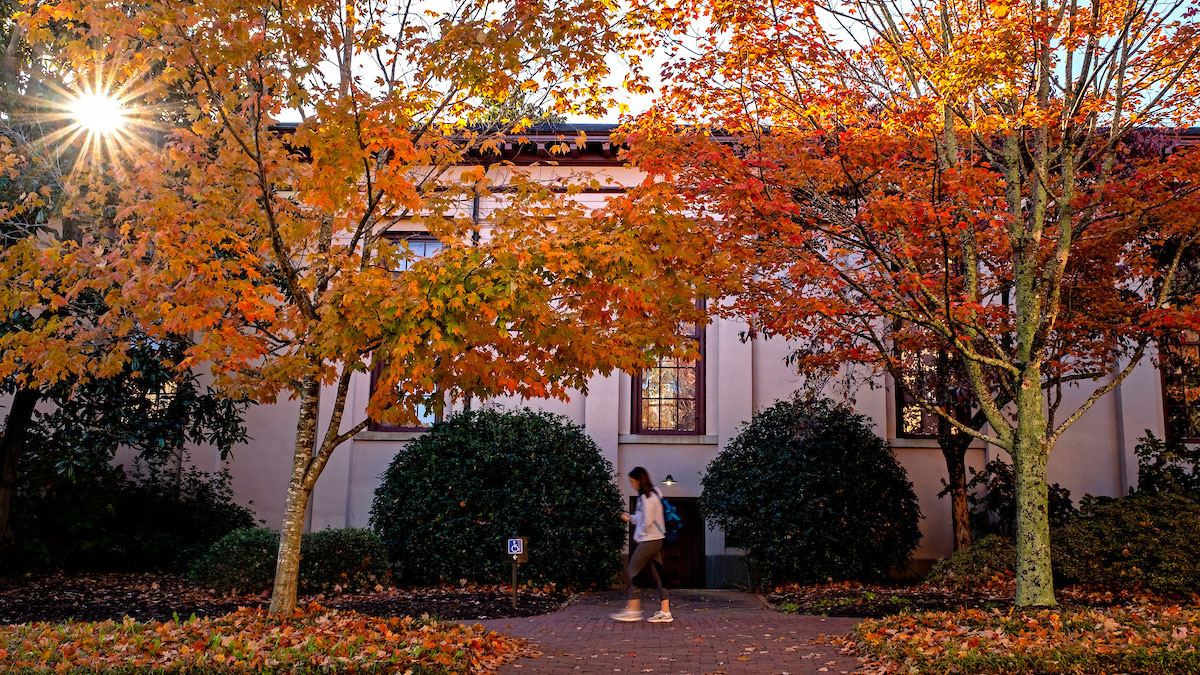 Students walk past trees with orange leaves.