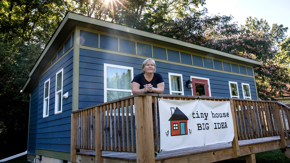 Amy Blank Wilson stands near a tiny home.