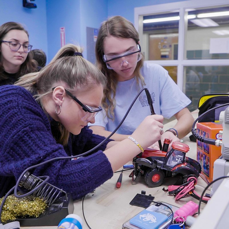 Students work to modifiy a toy's wiring.