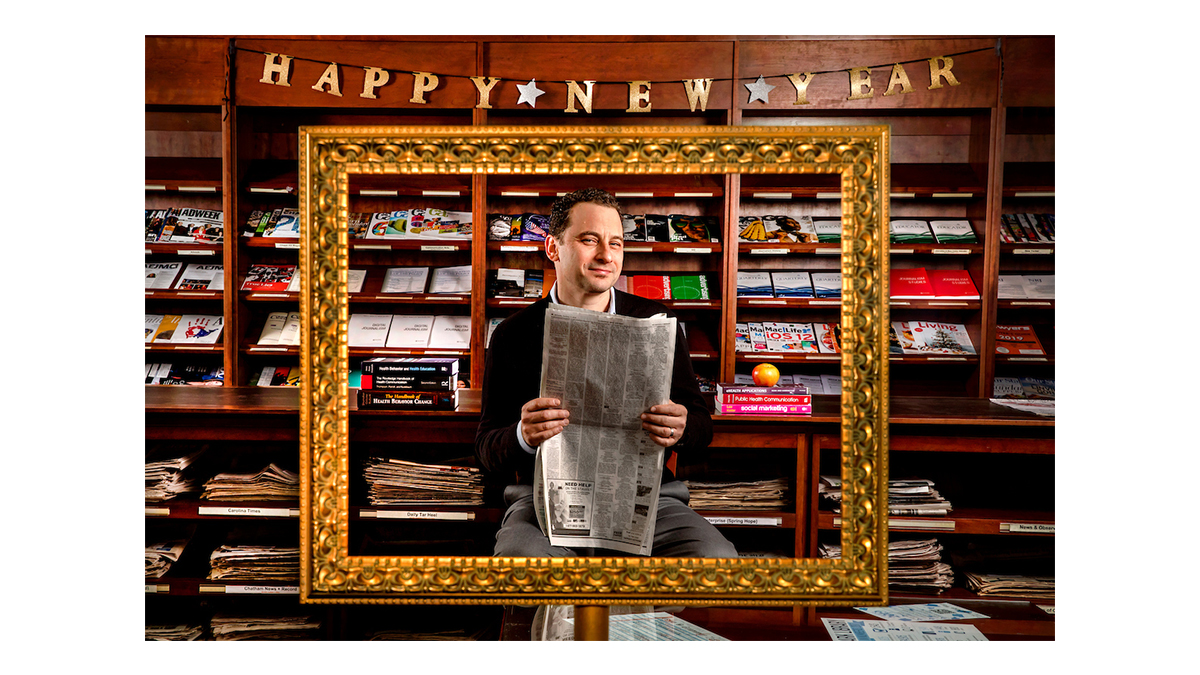 Noar holds a newspaper beneath a Happy New Year banner