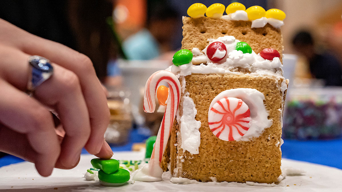 A student places gumdrops near her gingerbread house.