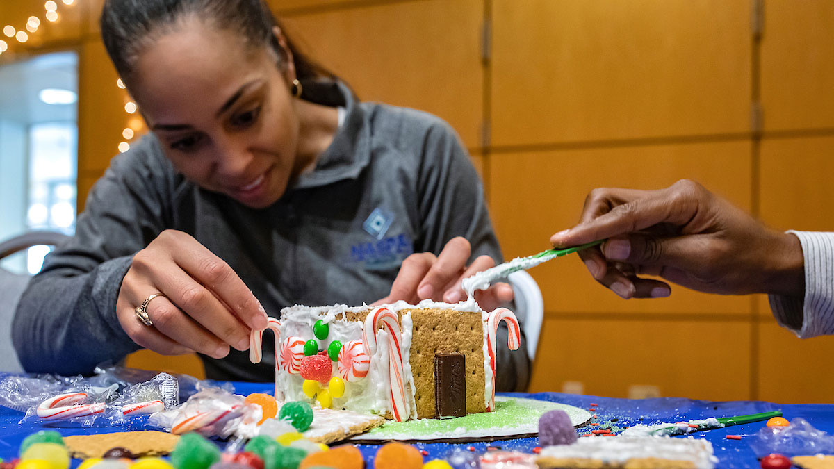 Two students build a gingerbread house.