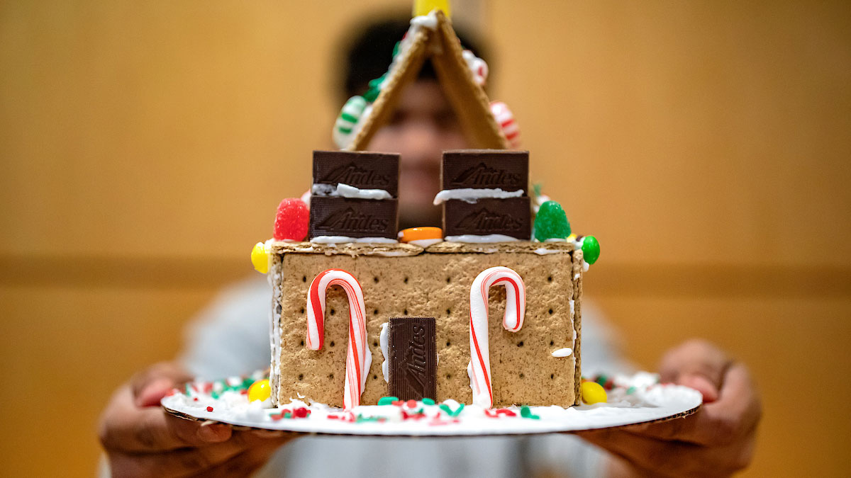 A student showcases his gingerbread house.