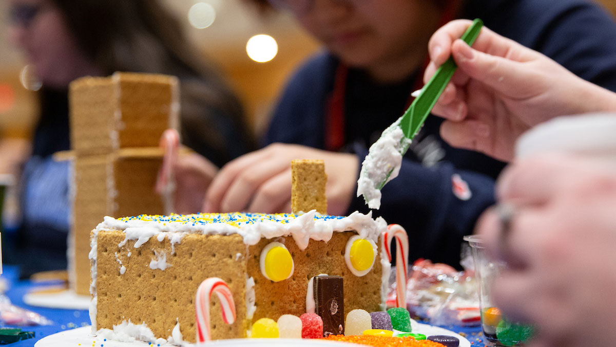 A student builds a gingerbread house.