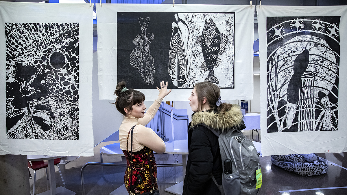 Two women look at a screenprint.