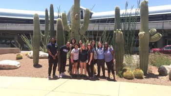 Student pose for a photo by cacti